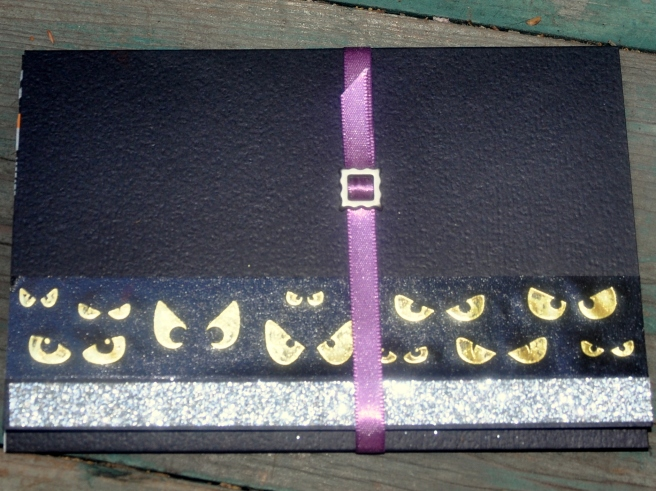 A different tri-fold card, closed with a band of ribbon and a tiny buckle