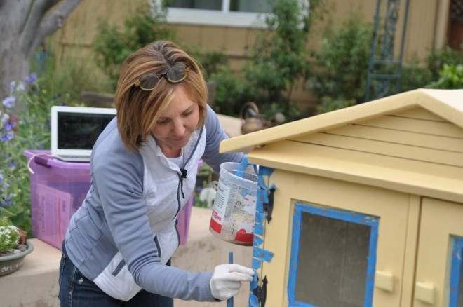 Donna Pierre painting the Little Free Library