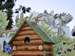 Flying bird cut-out above the log cabin birdhouse