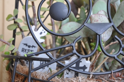 Succulents hold court in a cat-shaped plant stand with a few miniature tombstones